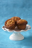 Three Sticky Cinnamon Rolls on a Small Pedestal Dish