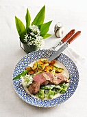 Sadler of lamb with a ramson and bean medley and fried potatoes