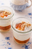 Layered desserts with apricot compote, creamy yoghurt and biscuit crumbs