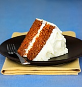 A slice of carrot cake topped with cream