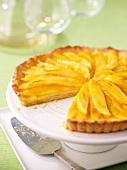 A mango tart on a cake stand, sliced