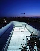 Durch transparenten Boden beleuchtete Dachterrasse unter städtischem Abendhimmel