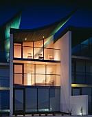 Modernes Gebäude mit abendlich beleuchteter Glasfassade und segelförmig aufgebogenem Dach mit grünem Lichteffekt