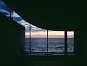 Skulpturaler, unbeleuchteter Innenraum mit Blick durch Glasfassade auf Abendhimmel über dem Meer