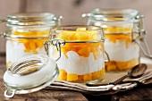 Fresh mango with yogurt in jars