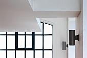 Ausschnitt einer abgehängten Decke vor Fenster mit schwarzen Sprossen und modernen Wandlampen