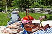 A picnic and alpine meadow with bread, bacon, cheese, sausages, tomatoes and wine