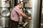 Brauer entnimmt Bierprobe vom Lagertank