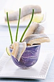 Soused herring fillets in a blue cup