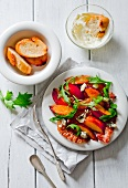 A salad made with roasted peaches, bacon, blue cheese, walnuts and rocket with toasted bread