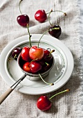 Sour cherries in a tea strainer on a plate