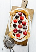 A cake topped with cherries, jam and mascarpone