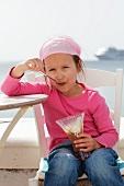 A little girl eating a chocolate ice cream sundae on a beach