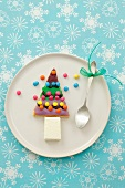 A Christmas tree shaped biscuit with ice cream and colourful chocolate beans