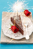 A slice of chocolate cake decorated with a sparkler and red roses