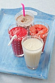 Four milkshakes (banana, chocolate, strawberry, raspberry)