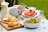 Scrambled egg with spinach, tomato salad with balsamic vinegar and a baguette
