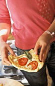 A person holding a slice of tomato pizza