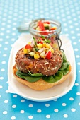A burger and sweetcorn salsa on a bread roll half
