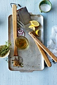 Barbecue utensils and ingredients (herb oil, lemons, thyme, onions, salt)