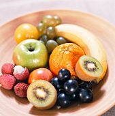A bowl of grapes, apples and exotic fruits