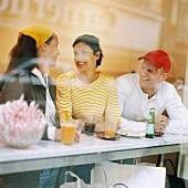 Zwei Frauen und ein Mann mit Getränken in einem Cafe