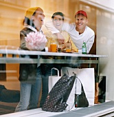 Two women and a man in a cafe taking a break from shopping