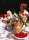 A summery table laid with strawberries and flowers