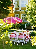 A summer garden table with a sunshade in front of a house