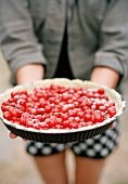 A woman holding a cherry pie
