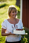 A woman serving a strawberry cake in a garden