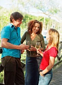 Friends with glasses of wine on a wooden bridge