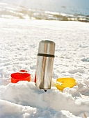 A Thermos flask and plastic cutlery in snow