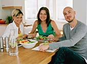 Friends eating salad in a kitchen
