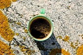 A cup of coffee on a rock, seen from above