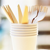 Wooden cutlery in a stack of paper cups