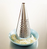 A cheese grater and grated cheese