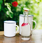 A bottle of water and enamel mugs