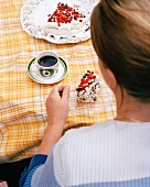 A woman eating a berry cake with coffee