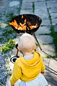 A little girl looking at a barbecue