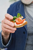A man holding a slice of bread topped with tomatoes and basil