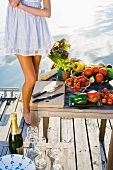 A woman on a jetty with vegetables and champagne