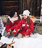 A mother and daughter grilling sausages on a open fire in front of a mountain hut