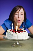 A woman blowing out candles on a birthday cake