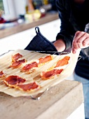 A person removing a sheet of paper with ham from an oven rack