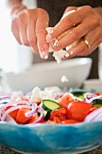Greek salad being sprinkled with feta cheese