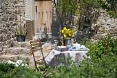 Gedeckter Frühstückstisch im Garten mit gelbem Blumenstrauss vor mediterranem Natursteinhaus