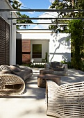 Licht- und Schattenspiel auf moderner Terrasse mit ausladenden aber filigran gearbeiteten Loungemöbeln und Tischen aus alten Stämmen tropischer Bäume