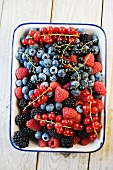 Various fresh berries in an enamel bowl