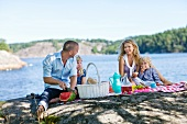 A young family having a picnic by a lake